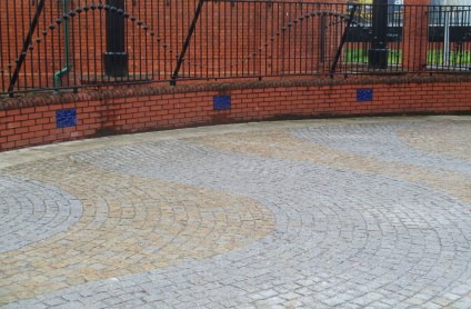 Arcing, curving bricks/Earth tones in concentric waves/Even the fence bobs