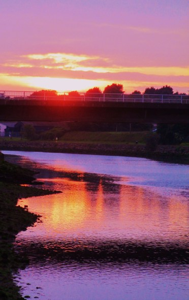 Drogheda sunset/Red-violet hues in the sky/Also curve in sea