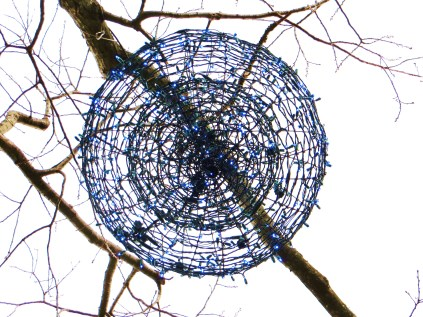 """From below: a giant blue """"egg"""" suspended from a tree"""