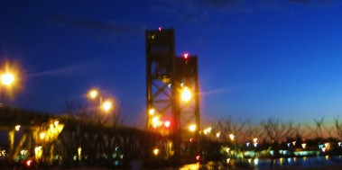 Memorial Bridge/Its massive moving towers/Are lit up at night